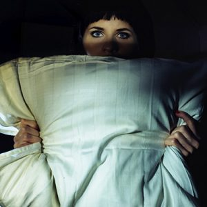 old movie still styled image of a woman holding a pillow in the darkness